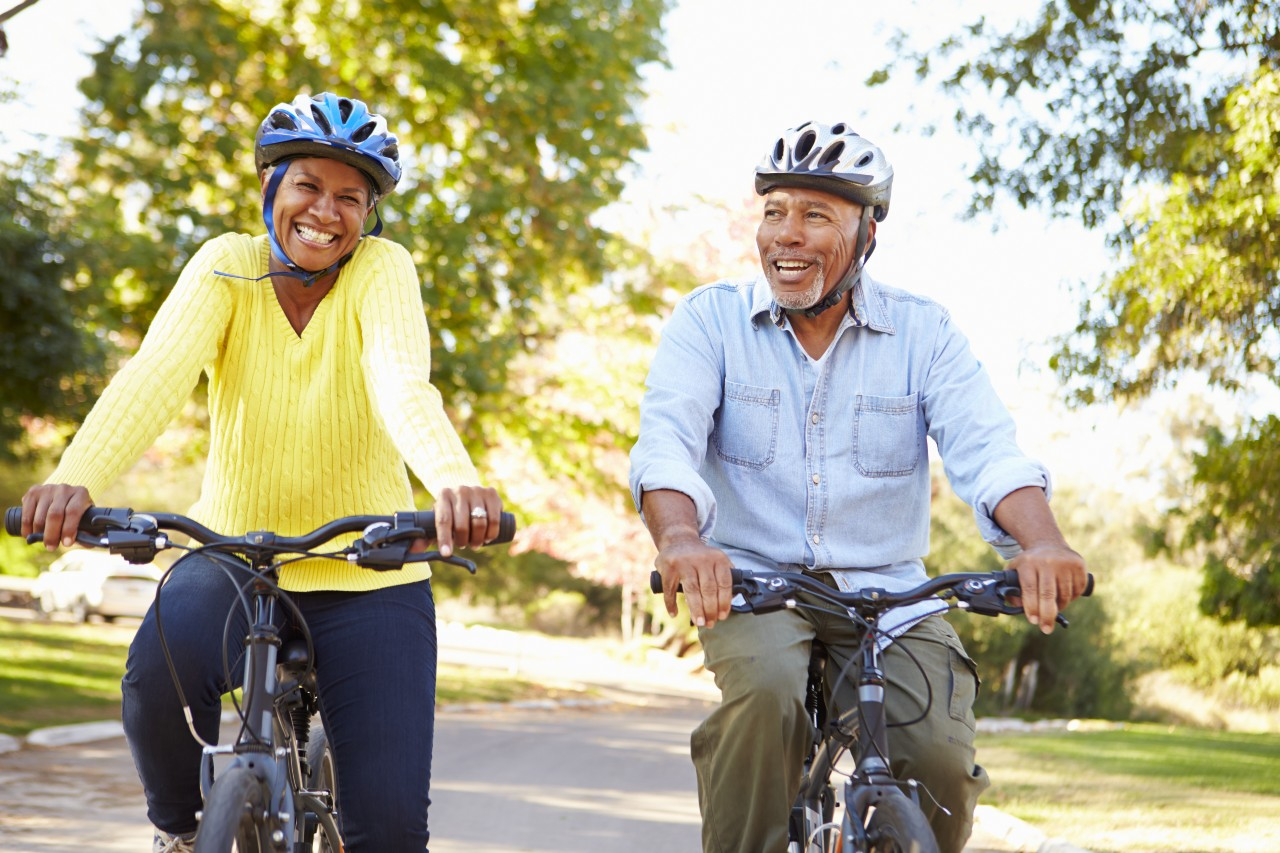 Happy couple riding bicycles wearing helmets