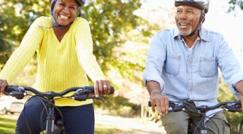 Older couple riding bicycles wearing helmets