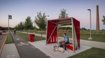 Man with dog waiting at red bus shelter at the museum